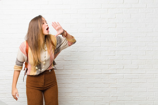 Giovane donna che urla ad alta voce e rabbiosamente per copiare lo spazio sul lato, con la mano accanto alla bocca