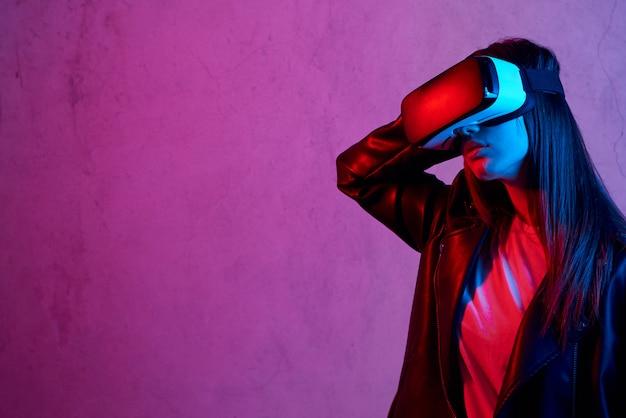 Giovane donna che usando il casco di realtà virtuale mentre indossa una giacca
