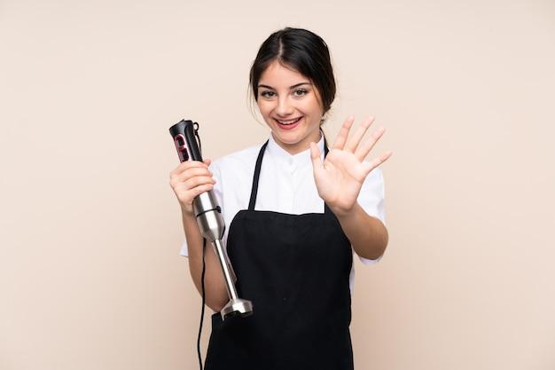 Giovane donna che usando il frullatore a immersione che saluta con la mano con l'espressione felice