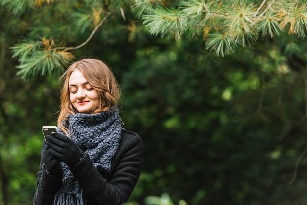 Giovane donna che usando smartphone vicino a conifere ramoscelli