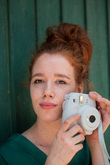 Giovane donna che usando una macchina fotografica d'epoca