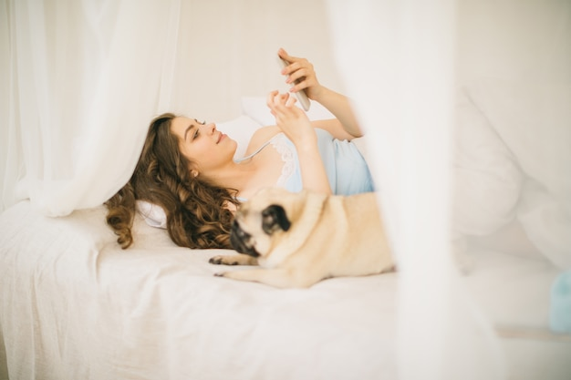 Giovane donna che utilizza cellulare nel letto. il piccolo cane del carlino sta trovandosi accanto a lei