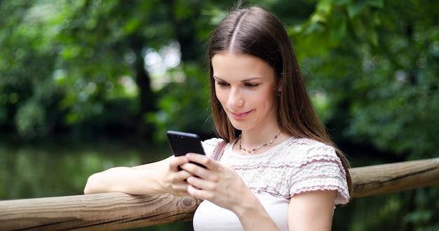 Giovane donna che utilizza il suo smartphone in un parco