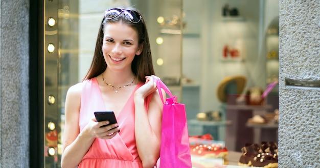 Giovane donna che utilizza il suo smartphone mentre comperando in una città