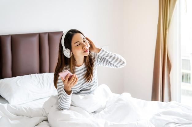 Giovane donna che utilizza le cuffie per ascoltare la musica