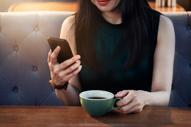 Giovane donna che utilizza smartphone in cafe o ristorante. bere tè o caffè caldo