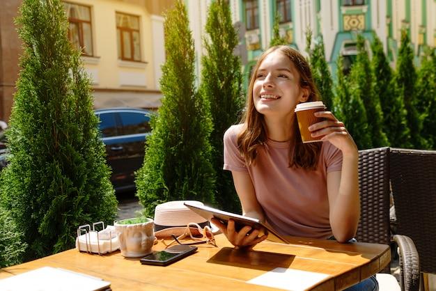 Giovane donna che utilizza tablet pc in un caffè su una terrazza estiva
