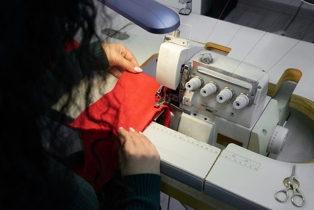 Giovane donna che utilizza una macchina per cucire di tagliacuci professionale nello studio dell'officina