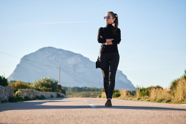Giovane donna che va sulla strada contro la splendida vista