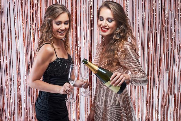 Giovane donna che versa champagne nei bicchieri.