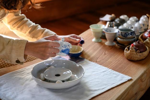 Giovane donna che versa tè caldo in tazza da the