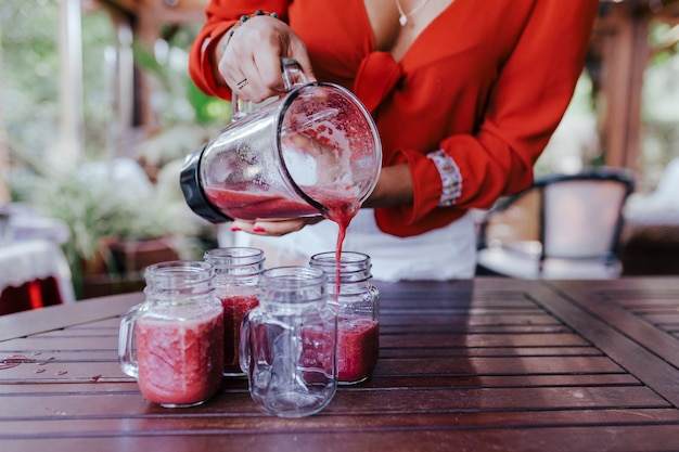Giovane donna che versa una sana ricetta di diversi frutti, anguria, arancia e more. usando un mixer. fatto in casa, al chiuso, stile di vita sano
