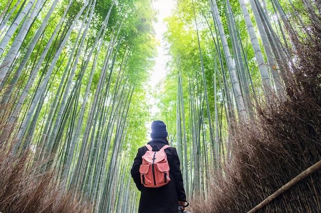 Giovane donna che viaggia a arashiyama bamboo grove, viaggiatore asiatico felice che osserva la foresta di bambù di sagano. punto di riferimento e popolare per le attrazioni turistiche di kyoto, in giappone. concetto di viaggio in asia