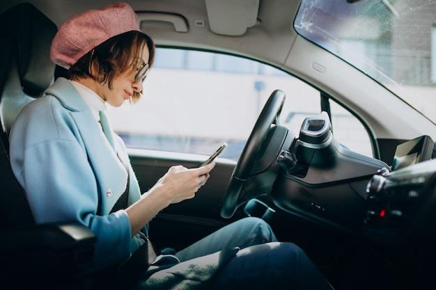 Giovane donna che viaggia in auto elettrica