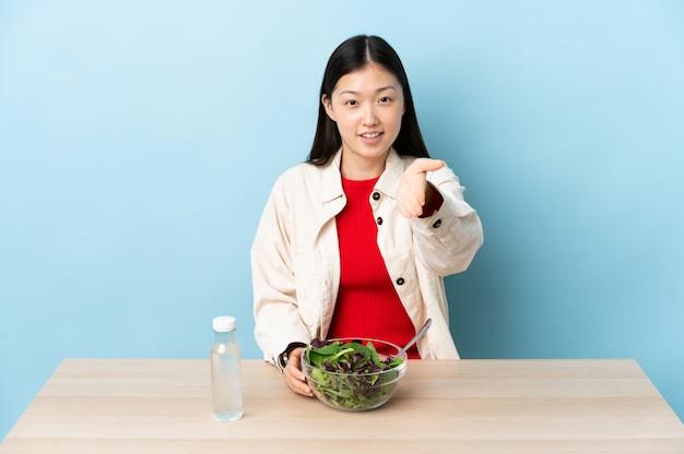 Giovane donna cinese che mangia un'insalata che stringe le mani per chiudere molto