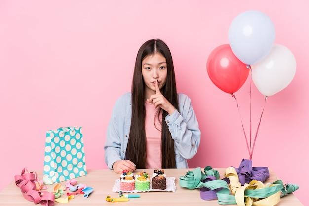 Giovane donna cinese che organizza un compleanno isolato mantenendo un segreto o chiedendo silenzio.