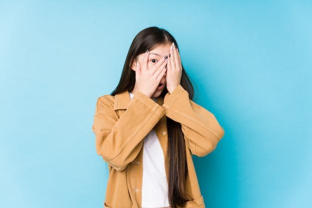 Giovane donna cinese che posa in un batter d'occhio isolato blu tramite le dita spaventate e nervose.
