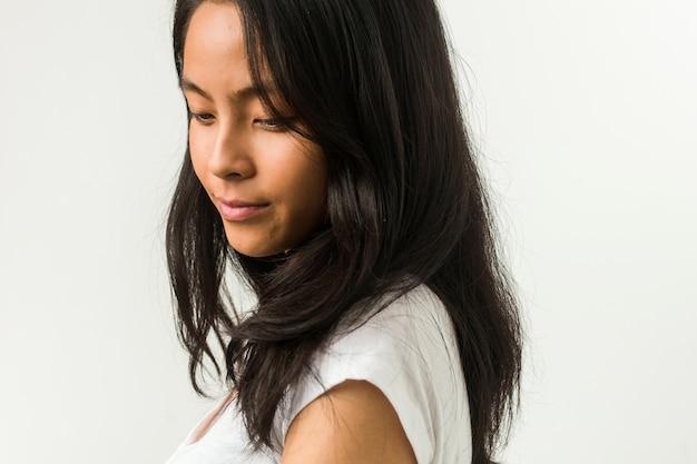 Giovane donna cinese che posa su una parete bianca