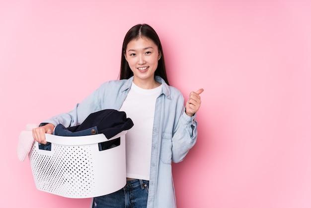 Giovane donna cinese che prende i vestiti sporchi isolati sorridendo e alzando il pollice in su