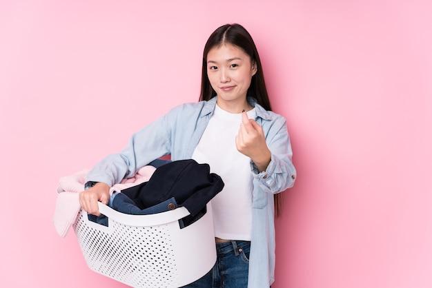 Giovane donna cinese che raccoglie vestiti sporchi isolati puntando il dito contro di te come se invitando ad avvicinarsi.