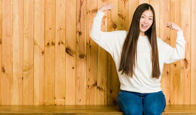 Giovane donna cinese che si siede su un posto di legno che mostra gesto di forza con le braccia, simbolo del potere femminile