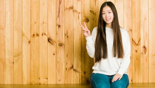 Giovane donna cinese che si siede su un posto di legno che mostra il segno di vittoria e che sorride ampiamente.