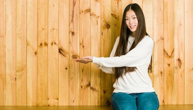 Giovane donna cinese che si siede su un posto di legno che tiene a su una palma.