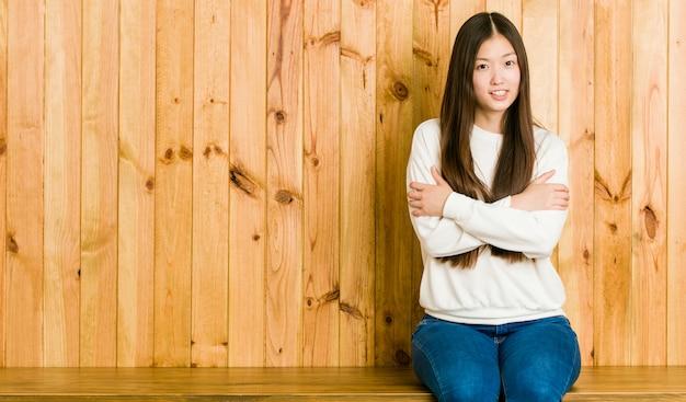 Giovane donna cinese che si siede su un posto di legno che va freddo a causa della bassa temperatura o di una malattia.