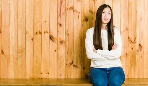 Giovane donna cinese che si siede su un posto di legno stanco di un compito ripetitivo.