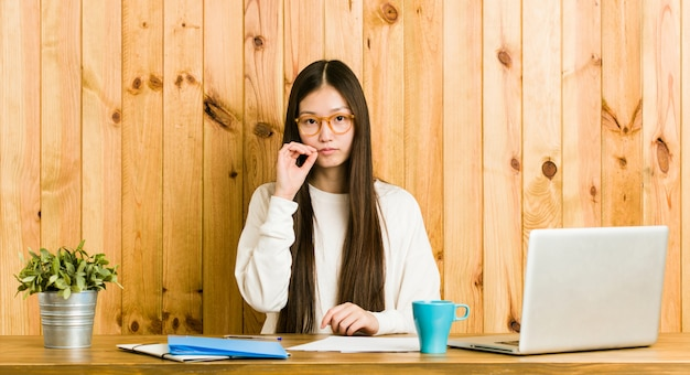 Giovane donna cinese che studia sulla sua scrivania con le dita sulle labbra mantenendo un segreto.