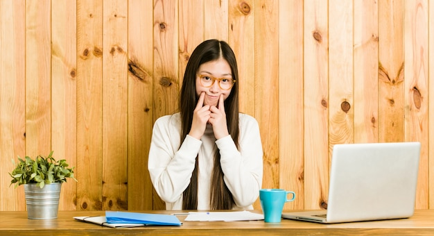 Giovane donna cinese che studia sulla sua scrivania dubitando tra due opzioni.
