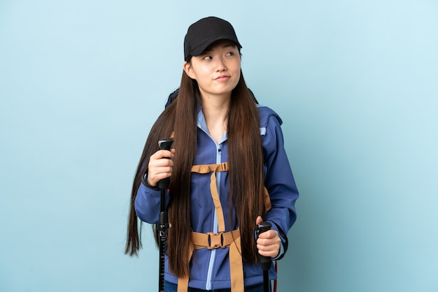 Giovane donna cinese con i pali di trekking e dello zaino sopra la parete blu isolata che ha dubbi mentre osservando in su