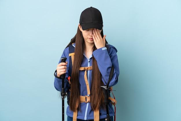 Giovane donna cinese con lo zaino e pali di trekking sopra la parete blu isolata con l'espressione stanca e malata