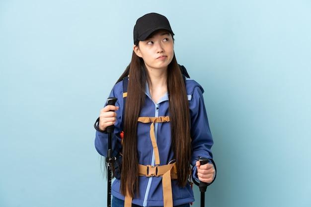 Giovane donna cinese con lo zaino e pali di trekking sopra la parete blu isolata e cercare
