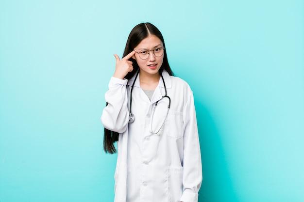 Giovane donna cinese del medico che mostra un gesto di delusione con l'indice.