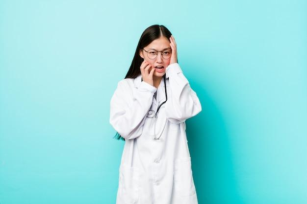 Giovane donna cinese del medico che si lamenta e che piange in modo sconsolato.