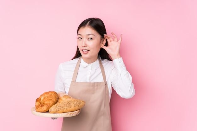 Giovane donna cinese del panettiere che prova ad ascoltare un gossip.