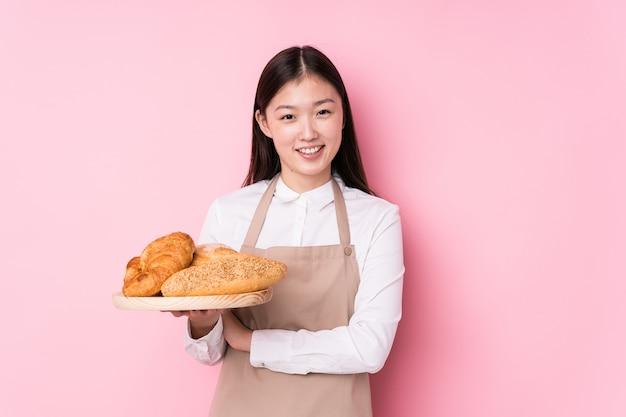 Giovane donna cinese del panettiere isolata ridendo e divertendosi.