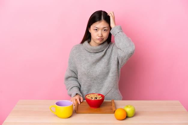 Giovane donna cinese facendo colazione in un tavolo con un'espressione di frustrazione e non comprensione
