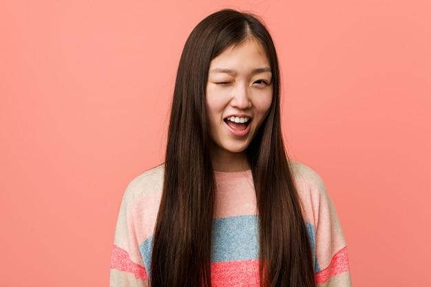 Giovane donna cinese fredda che sbatte le palpebre, divertente, amichevole e spensierata.
