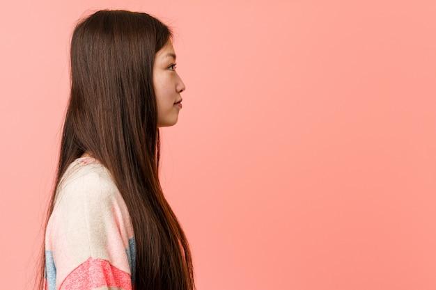 Giovane donna cinese fresca che guarda a sinistra, posa laterale.