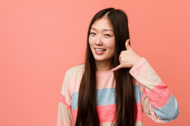 Giovane donna cinese fresca che mostra un gesto di chiamata di telefono cellulare con le dita.