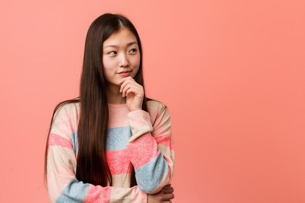 Giovane donna cinese fresca che osserva lateralmente con espressione dubbiosa e scettica.