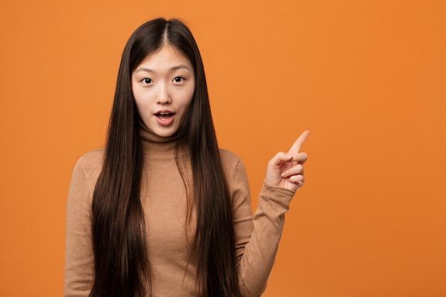 Giovane donna cinese graziosa che indica il lato