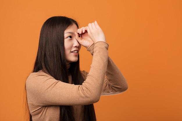Giovane donna cinese graziosa che sembra lontana che lo tiene mano sulla fronte.