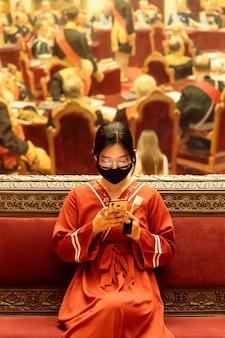 Giovane donna cinese in abiti nazionali che indossa una maschera chirurgica seduto nel museo, utilizzando smartphone. il nuovo tipo di polmonite da coronavirus si è diffuso nei paesi europei.