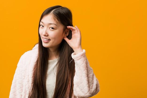 Giovane donna cinese in pigiama cercando di ascoltare un gossip.