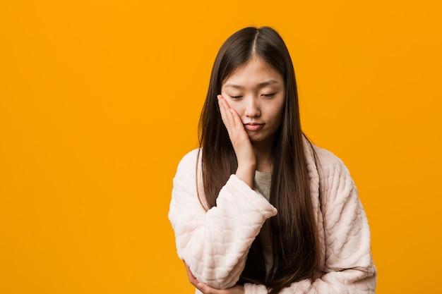 Giovane donna cinese in pigiama che è annoiata, affaticata e ha bisogno di una giornata di relax.