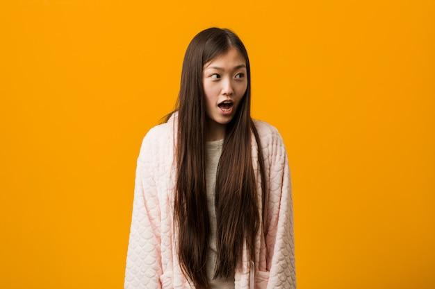 Giovane donna cinese in pigiama essere scioccata a causa di qualcosa che ha visto.