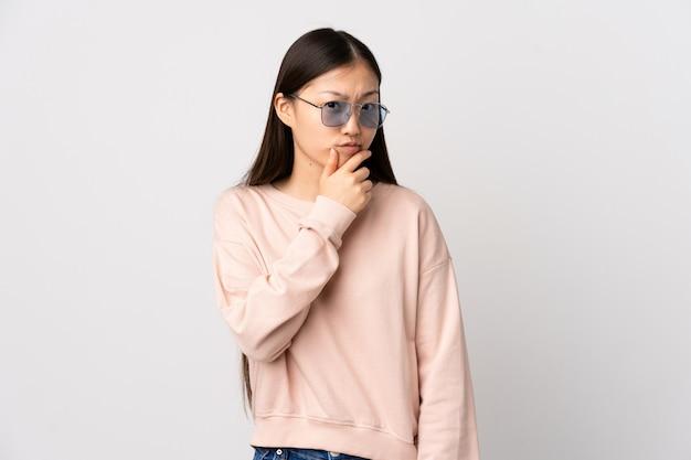 Giovane donna cinese sopra la parete bianca isolata che ha dubbi